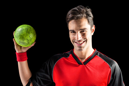 elbow band: Portrait of happy athlete man holding a ball on black background