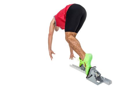 starting blocks: Male athlete running from starting blocks on white background