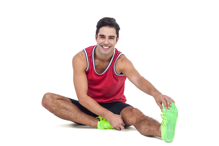 hamstring: Portrait of male athlete stretching his hamstring on white background