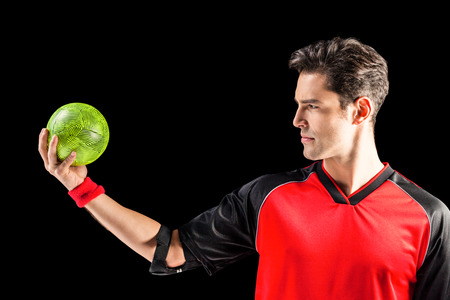 elbow band: Confident athlete man holding a ball on black background