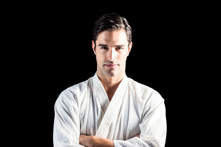 karateka: Portrait of fighter standing on black background with arms crossed Stock Photo