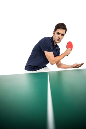 Confident male athlete playing table tennis on white background Stock Photo
