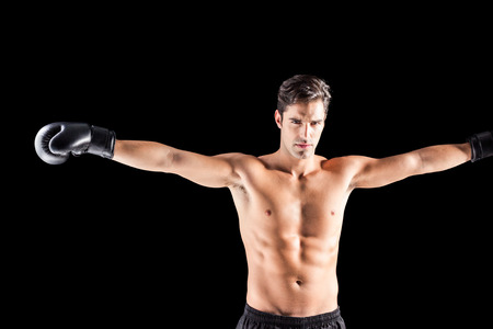 outstretched: Boxer standing with arms outstretched on black background Stock Photo