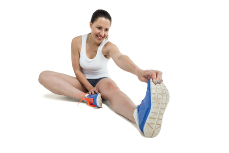 hamstring: Athlete woman stretching her hamstring on white background