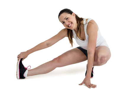 hamstring: Happy athlete woman stretching her hamstring on white background