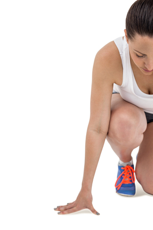 cut the competition: Athlete woman in ready to run position on white background