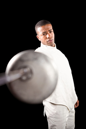 fencing sword: Portrait of swordsman practicing with fencing sword on black background