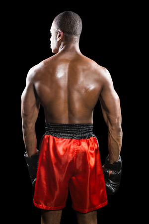rear: Rear view of boxer standing on black background