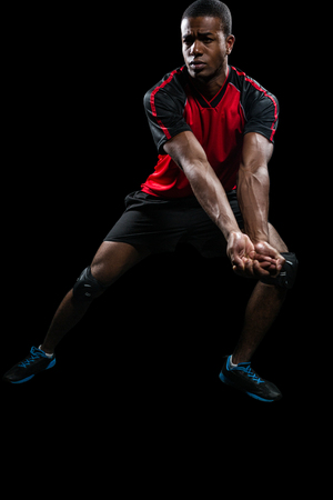 cut the competition: Sportsman posing while playing volleyball on black background