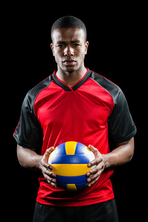 sportsman: Sportsman holding a volleyball on black background