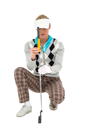 cut the competition: Female golf player kneeling with a golf club on white background
