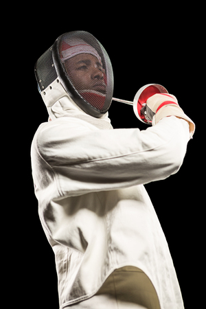 fencing sword: Man wearing fencing suit practicing with sword on black background