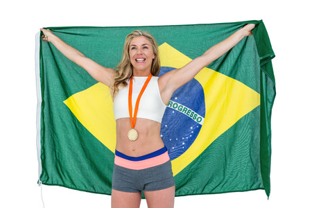 Athlete with gold medal around his neck posing with brazilian flag after victory on white background
