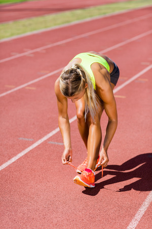 athleticism: Female athlete tying her shoe laces on running track on a sunny day
