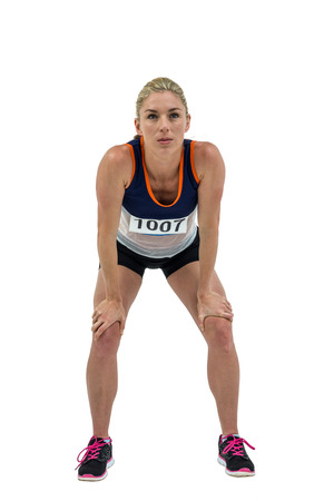 knee bend: Tired athlete standing with hand on knee on white background Stock Photo