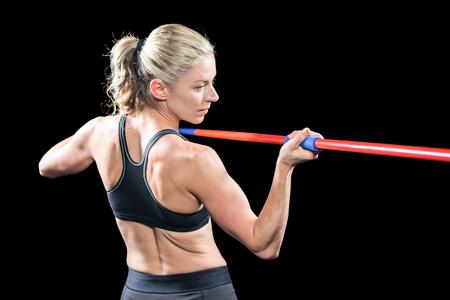 javelin: Athlete preparing to throw javelin on black background