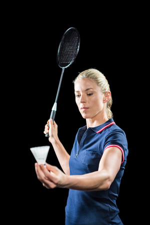 racquet: Badminton player holding a racquet ready to serve on black background