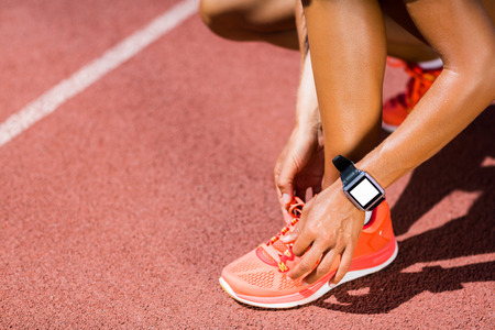 shoe laces: Female athlete tying her shoe laces on running track on a sunny day