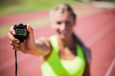 stop watch: Female athlete showing stop watch on running track