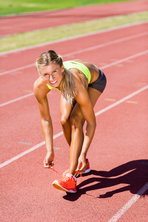 athleticism: Portrait of female athlete tying her shoe laces on running track on a sunny day