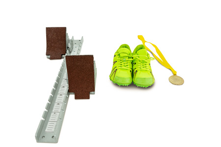 starting block: Trainer shoes, starting block and gold medal on isolated white background