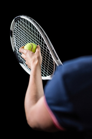 racquet: Tennis player holding a racquet ready to serve on black background