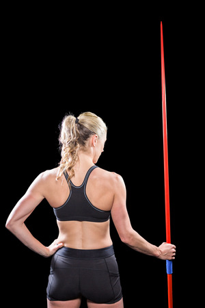 javelin: Rear view of athlete standing with javelin on black background Stock Photo