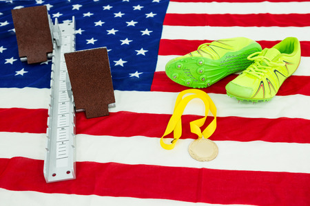 starting block: Green trainer shoes, starting block and gold medal on american flag