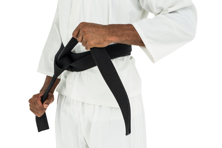 tightening: Mid section of fighter tightening karate belt on white background