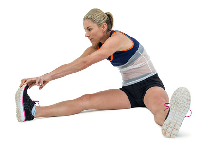 hamstring: Athletic woman stretching her hamstring on white background