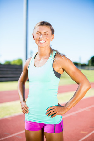 athleticism: Happy female athlete standing with hand on hip on running track