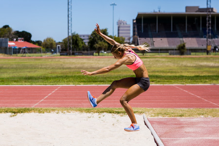 long jump: Female athlete performing a long jump during a competition