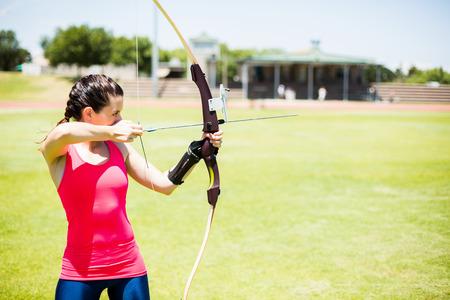 athleticism: Female athlete practicing archery in stadium