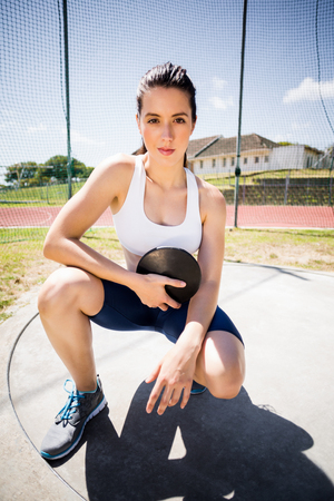 discus: Portrait of confident female athlete holding a discus in stadium