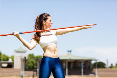 lanzamiento de jabalina: De la mujer atleta a punto de lanzar una jabalina en el estadio