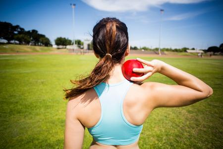 lanzamiento de bala: Vista trasera de la mujer atleta que se prepara para lanzar bola de tiro puesto en estadio