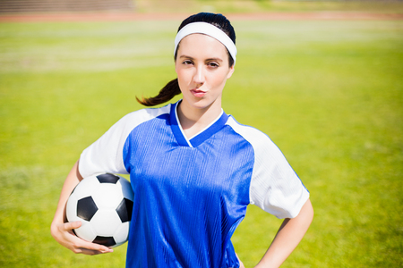 athleticism: Confident soccer player standing in stadium with a ball Stock Photo