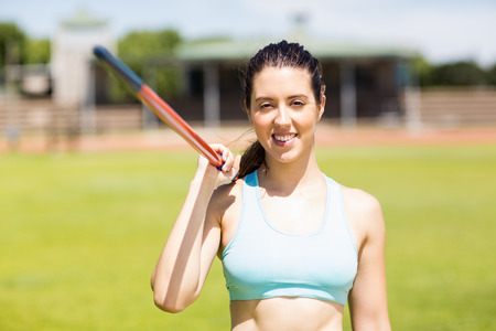 javelin: Portrait of happy female athlete holding a javelin in stadium Stock Photo