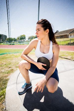 discus: Confident female athlete holding a discus in stadium
