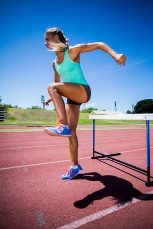 athleticism: Female athlete jumping above the hurdle during the race Stock Photo