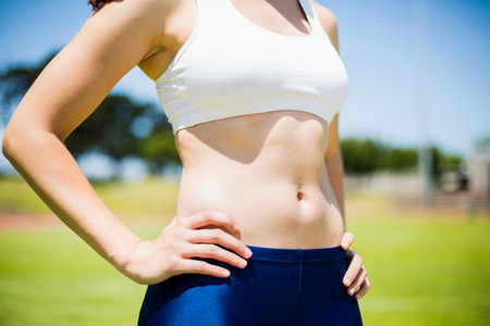 athleticism: Mid-section of female athlete standing with hand on hip in stadium Stock Photo