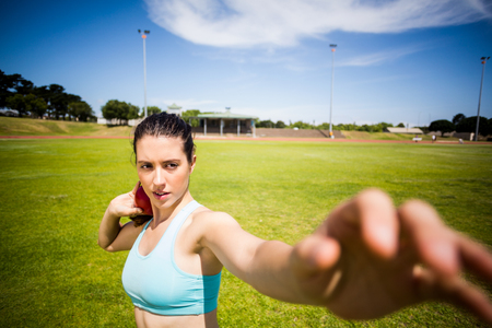 put: Female athlete preparing to throw shot put ball in stadium
