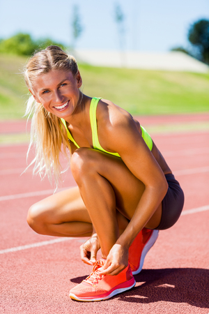 shoe laces: Portrait of female athlete tying her shoe laces on running track on a sunny day