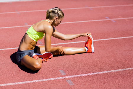 athleticism: Female athlete warming up on the running track on a sunny day Stock Photo