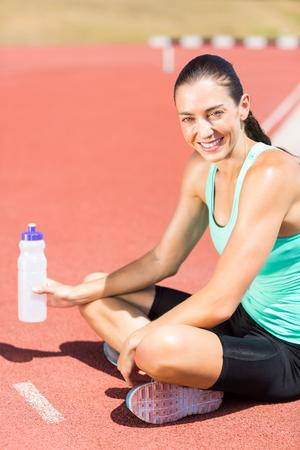 tomando refresco: Retrato de la mujer atleta cansado que se sienta en la pista de atletismo con la botella de agua