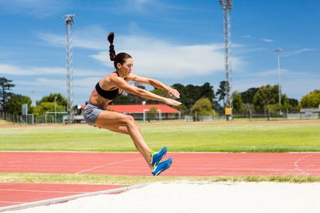 salto largo: Atleta femenina realizar un salto de longitud durante una competici�n Foto de archivo