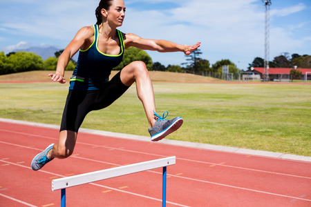 Female athlete jumping above the hurdle during the race Stock Photo