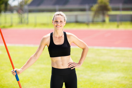 athleticism: Portrait of happy female athlete holding a javelin standing in stadium Stock Photo