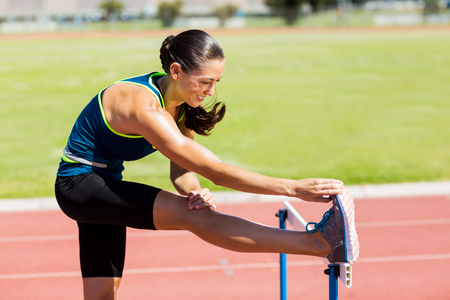 hurdle: Female athlete warming up above hurdle on running track