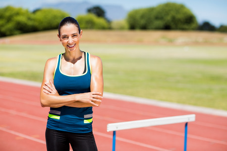 hurdle: Portrait of female athlete standing beside hurdle with arms crossed
